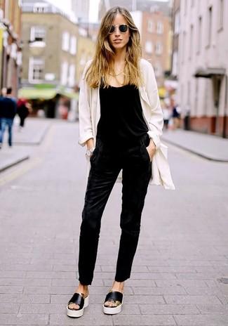 Comment porter: cache-poussière blanc, combinaison pantalon noire, sandales plates en cuir noires et blanches, lunettes de soleil noires