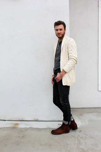 Comment porter: cardigan à col châle beige, pull à col boutonné gris foncé, jean noir, bottes de loisirs en daim marron