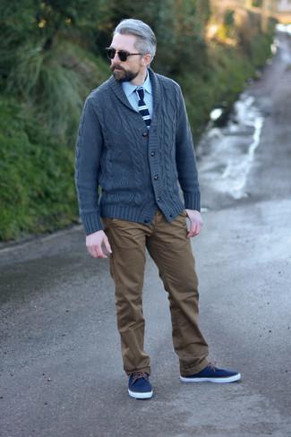 Comment porter un pantalon chino marron: Un cardigan à col châle gris foncé et un pantalon chino marron sont un choix de tenue idéale à avoir dans ton arsenal. Tu veux y aller doucement avec les chaussures? Choisis une paire de des baskets basses en toile bleu marine pour la journée.