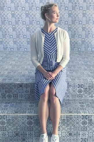 Comment porter des baskets basses blanches: Associe un cardigan blanc avec une robe midi à rayures verticales bleue pour obtenir un look relax mais stylé. Jouez la carte décontractée pour les chaussures et fais d'une paire de des baskets basses blanches ton choix de souliers.