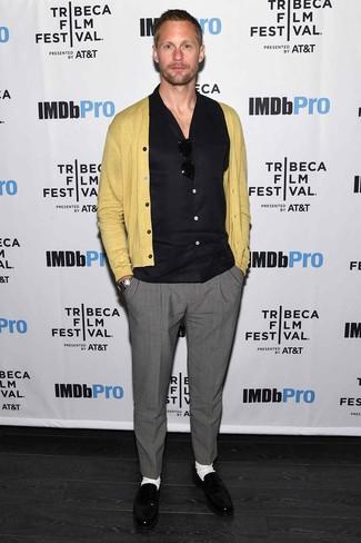 Tenue de Alexander Skarsgård: Cardigan moutarde, Chemise à manches courtes noire, Pantalon de costume gris, Slippers en cuir noirs