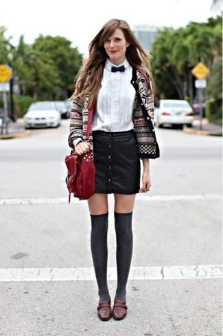 Comment porter: cardigan en jacquard gris, chemise de ville blanche, jupe boutonnée en cuir noire, slippers en cuir marron foncé