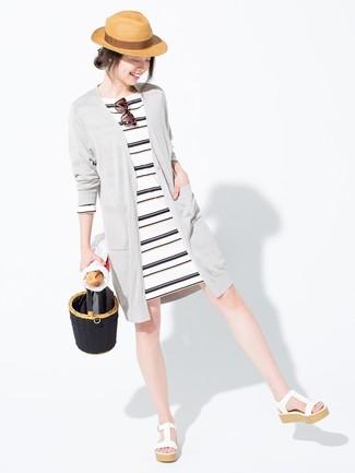 Choisis un cardigan long gris et une robe décontractée à rayures horizontales blanche et noire pour une impression décontractée. Une paire de des sandales compensées en cuir blanches apportera une esthétique classique à l'ensemble.