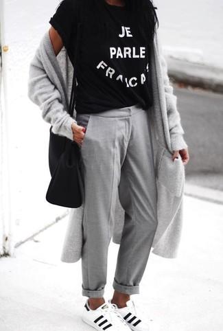 """Si tu es une fille plutôt """"jean t-shirt"""", tu vas aimer le combo simple d'un cardigan long gris Maison Margiela et d'un pantalon chino gris. Termine ce look avec une paire de des baskets basses en cuir blanches et noires."""