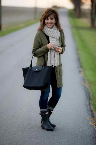 Comment porter: cardigan long olive, t-shirt à manche longue noir, jean skinny bleu marine, bottes de pluie noires