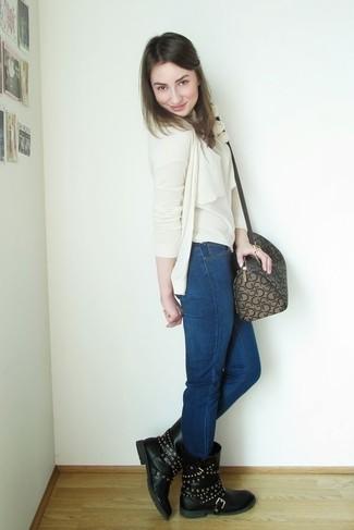 Comment porter: cardigan beige, top sans manches beige, jean skinny bleu marine, bottes mi-mollet en cuir à clous noires