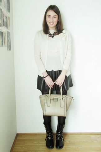 Associe un cardigan beige avec une jupe patineuse en cuir noire pour obtenir un look relax mais stylé. Transforme-toi en bête de mode et fais d'une paire de des bottes mi-mollet en cuir à clous noires ton choix de souliers.