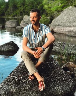 Comment porter: chemise à manches courtes à rayures verticales blanc et bleu, jean skinny olive, baskets à enfiler en toile imprimées multicolores, montre argentée