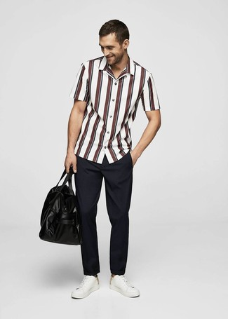Comment porter: chemise à manches courtes à rayures verticales blanc et rouge, pantalon chino bleu marine, baskets basses en cuir blanches, fourre-tout en cuir noir
