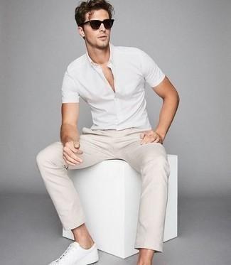 Comment porter des baskets basses en cuir blanches: Essaie d'associer une chemise à manches courtes blanche avec un pantalon chino beige pour un déjeuner le dimanche entre amis. Termine ce look avec une paire de baskets basses en cuir blanches.