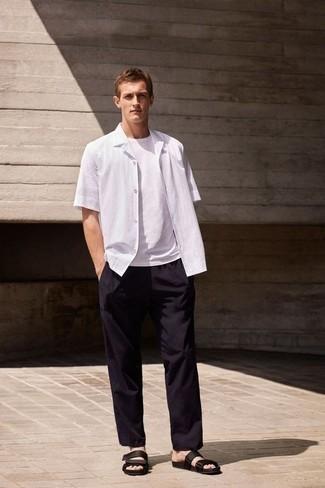 Comment porter une chemise à manches courtes blanche: Pour une tenue de tous les jours pleine de caractère et de personnalité pense à associer une chemise à manches courtes blanche avec un pantalon chino noir. Pour les chaussures, fais un choix décontracté avec une paire de des sandales en toile noires.