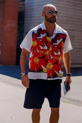 Tendances mode hommes: Harmonise une chemise à manches courtes à fleurs blanche avec un short bleu marine pour une tenue idéale le week-end.