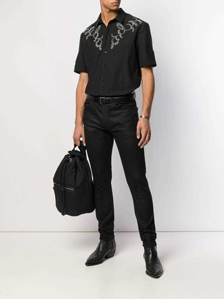Comment porter: chemise à manches courtes brodée noire, jean noir, bottines chelsea en cuir noires, sac à dos en toile noir