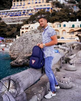 Comment porter: chemise à manches courtes imprimée blanc et bleu, jean bleu, chaussures de sport blanches, sac à dos en toile bleu marine