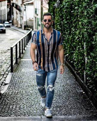 Comment porter: chemise à manches courtes à rayures verticales bleu marine, jean skinny déchiré bleu, baskets basses blanches, lunettes de soleil noires