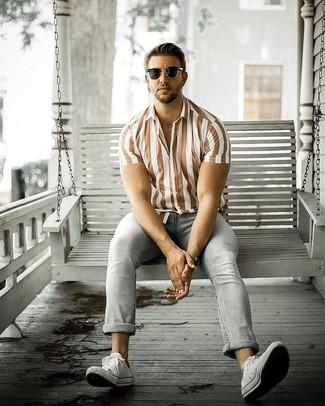 Comment porter: chemise à manches courtes en lin à rayures verticales marron, jean gris, baskets basses en toile blanches, lunettes de soleil noires