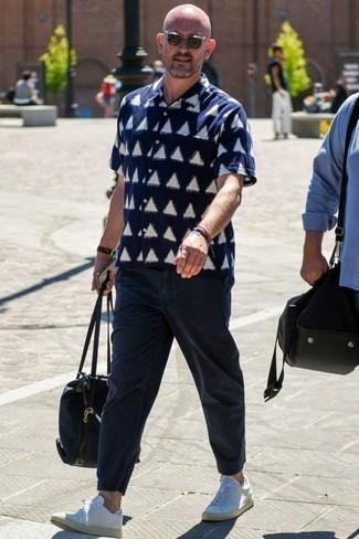 Comment porter un pantalon chino bleu marine: Pense à porter une chemise à manches courtes imprimée bleu marine et blanc et un pantalon chino bleu marine pour une tenue confortable aussi composée avec goût. Cet ensemble est parfait avec une paire de des baskets basses en cuir blanches.