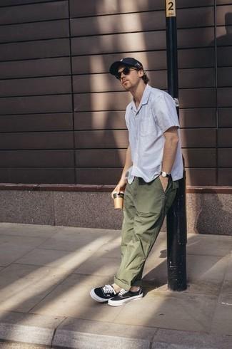 Comment porter un pantalon chino olive: Pense à porter une chemise à manches courtes blanche et un pantalon chino olive pour une tenue idéale le week-end. Termine ce look avec une paire de baskets basses en toile noires et blanches.