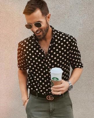 Comment porter: chemise à manches courtes á pois noire, pantalon chino olive, ceinture en cuir noire, lunettes de soleil noires