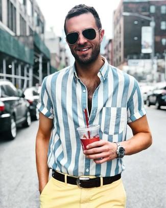 Comment porter: chemise à manches courtes à rayures verticales blanc et bleu, pantalon chino jaune, ceinture en cuir noire, lunettes de soleil noires