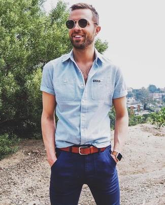 Comment porter: chemise à manches courtes à rayures verticales bleu clair, pantalon chino bleu marine, ceinture en cuir tabac, lunettes de soleil noires