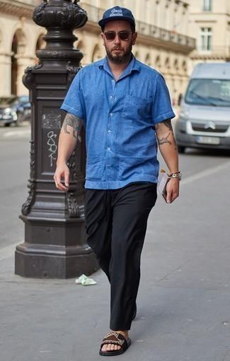 Comment s'habiller après 40 ans pour un style relax: Porte une chemise à manches courtes en chambray bleue et un pantalon chino noir pour une tenue idéale le week-end. Mélange les styles en portant une paire de des sandales en toile imprimées noires.