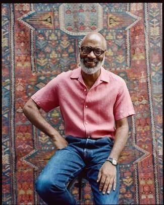 Comment s'habiller après 50 ans: Pour une tenue de tous les jours pleine de caractère et de personnalité choisis une chemise à manches courtes rose et un jean bleu marine.