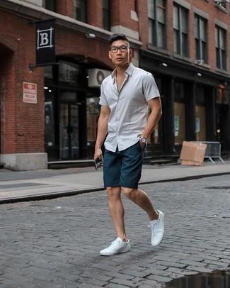 Tendances mode hommes: Porte une chemise à manches courtes blanche et un short bleu marine pour obtenir un look relax mais stylé. Assortis ce look avec une paire de baskets basses en toile blanches.