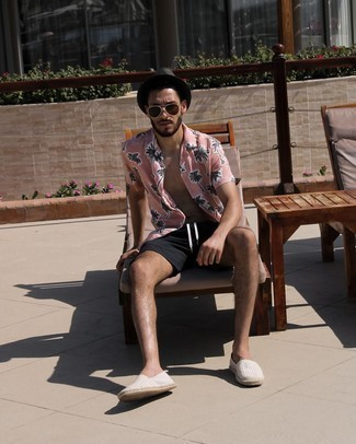 Tendances mode hommes: Pour une tenue de tous les jours pleine de caractère et de personnalité pense à marier une chemise à manches courtes imprimée rose avec un short noir. Cette tenue se complète parfaitement avec une paire de espadrilles en toile à rayures horizontales grises.