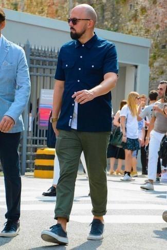 Comment porter une chemise à manches courtes avec des baskets basses: Pense à associer une chemise à manches courtes avec un pantalon chino vert foncé pour obtenir un look relax mais stylé. Cette tenue se complète parfaitement avec une paire de des baskets basses.