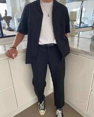 Comment porter une ceinture en cuir noire: Essaie de marier une chemise à manches courtes bleu marine avec une ceinture en cuir noire pour une tenue relax mais stylée. Jouez la carte classique pour les chaussures et opte pour une paire de des baskets basses en toile noires et blanches.