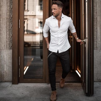 Comment porter: chemise à manches longues à rayures verticales blanche, jean skinny noir, bottes de loisirs en cuir marron