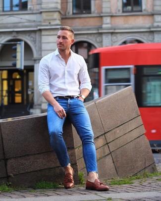 Comment porter: chemise à manches longues blanche, jean skinny bleu, mocassins à pampilles en cuir marron