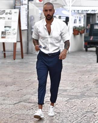 Comment porter une ceinture en cuir bleu marine: Essaie de marier une chemise à manches longues blanche avec une ceinture en cuir bleu marine pour un look confortable et décontracté. Assortis cette tenue avec une paire de des baskets basses blanches pour afficher ton expertise vestimentaire.