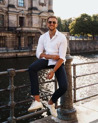 Comment porter un pantalon chino à rayures verticales bleu marine: Essaie d'associer une chemise à manches longues blanche avec un pantalon chino à rayures verticales bleu marine pour un look de tous les jours facile à porter. Cette tenue est parfait avec une paire de des baskets basses en cuir blanches.