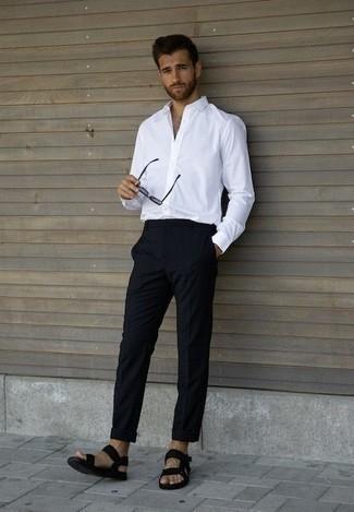 Comment porter un pantalon chino bleu marine: Essaie d'harmoniser une chemise à manches longues blanche avec un pantalon chino bleu marine pour obtenir un look relax mais stylé. D'une humeur créatrice? Assortis ta tenue avec une paire de des sandales en toile noires.