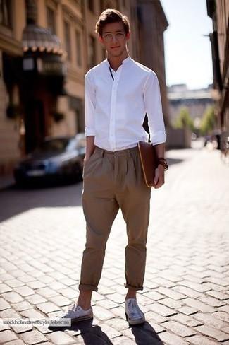 Tendances mode hommes: Les journées chargées nécessitent une tenue simple mais stylée, comme une chemise à manches longues blanche et un pantalon chino marron. Si tu veux éviter un look trop formel, complète cet ensemble avec une paire de des baskets basses en toile blanches.