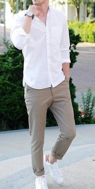 Comment porter une chemise à manches longues blanche: Pour créer une tenue idéale pour un déjeuner entre amis le week-end, marie une chemise à manches longues blanche avec un pantalon chino marron clair. Jouez la carte décontractée pour les chaussures et choisis une paire de des baskets basses en cuir blanches.