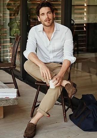 Comment porter un pantalon chino marron clair: Essaie de marier une chemise à manches longues blanche avec un pantalon chino marron clair pour obtenir un look relax mais stylé. Rehausse cet ensemble avec une paire de des slippers en daim marron foncé.