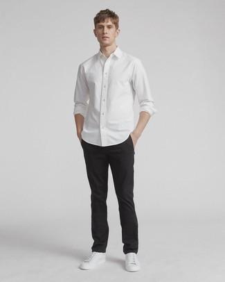 Comment porter un pantalon chino noir: Marie une chemise à manches longues blanche avec un pantalon chino noir pour un look de tous les jours facile à porter. Si tu veux éviter un look trop formel, termine ce look avec une paire de des baskets basses en cuir blanches.