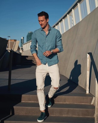Comment porter: chemise à manches longues en chambray bleu clair, jean déchiré blanc, baskets basses en daim bleu canard, montre argentée