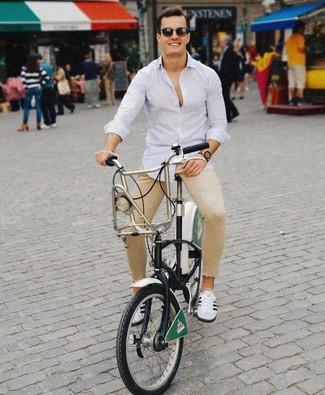 Comment porter: chemise à manches longues à rayures verticales bleu clair, jean skinny marron clair, baskets basses blanches et noires, lunettes de soleil marron foncé