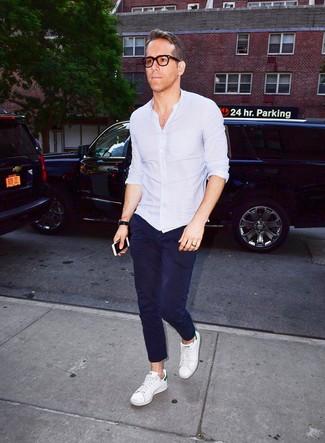 Comment porter: chemise à manches longues bleu clair, pantalon chino bleu marine, baskets basses en cuir blanches, montre en cuir noire