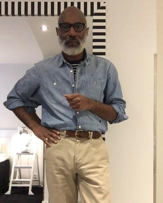 Comment porter: chemise à manches longues en chambray bleu clair, t-shirt à col rond à rayures horizontales noir et blanc, pantalon chino marron clair, ceinture en toile tressée beige