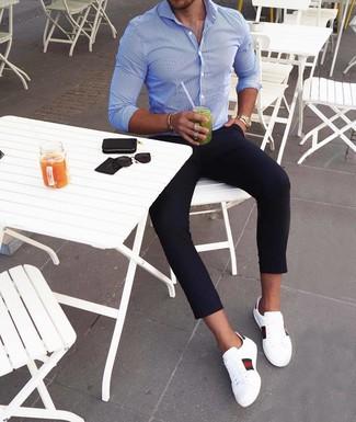 Comment porter: chemise à manches longues à rayures verticales bleue, pantalon chino bleu marine, baskets basses en cuir imprimées blanches, montre dorée