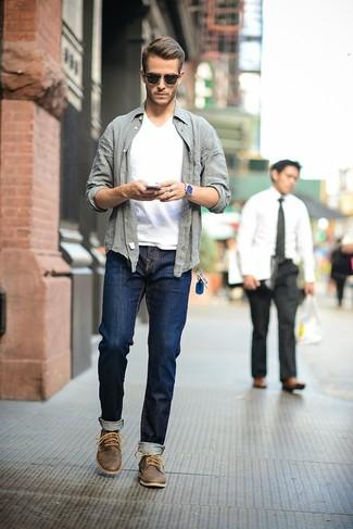 Associe une chemise à manches longues grise avec un jean bleu marine pour obtenir un look relax mais stylé. Assortis ce look avec une paire de des bottines chukka en cuir marron foncé.