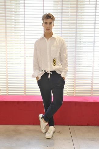 Comment porter: chemise à manches longues imprimée blanche, pantalon chino bleu marine, baskets basses en cuir blanches