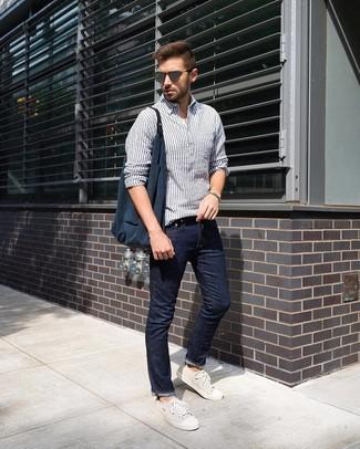 Comment porter: chemise à manches longues en lin à rayures verticales blanc et bleu marine, jean bleu marine, baskets basses en toile beiges, sac fourre-tout en toile bleu marine