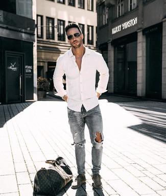 Comment porter: chemise à manches longues blanche, jean déchiré gris, bottines chukka en daim grises, fourre-tout en cuir imprimé marron foncé