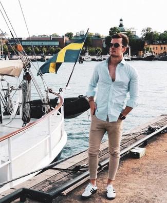 Comment porter: chemise à manches longues à rayures verticales vert menthe, jean skinny marron clair, baskets basses blanches et noires, lunettes de soleil noires